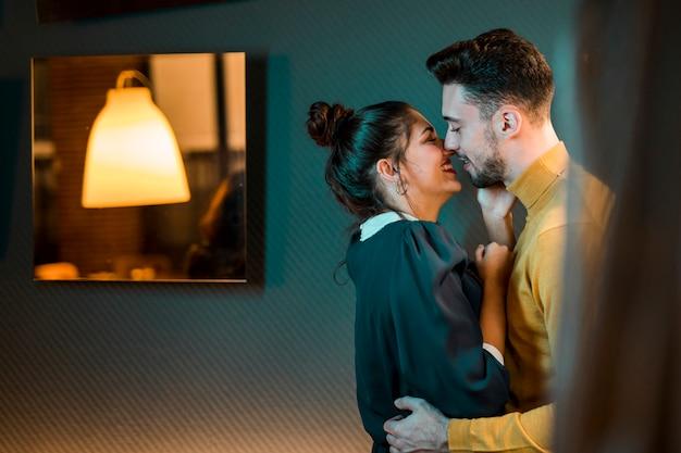 Heureux jeune homme embrassant une femme joyeuse dans la chambre Photo gratuit