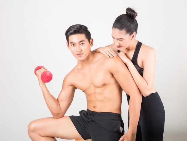 Heureux jeune homme de fitness et sa petite amie à l'entraînement Photo Premium