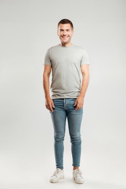 Heureux Jeune Homme Habillé En T-shirt Gris Isolé Sur Mur Gris Photo gratuit