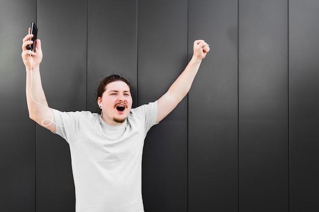 Heureux jeune homme levant les bras en écoutant de la musique au casque contre un mur noir Photo gratuit