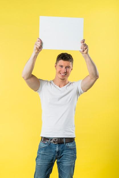 Heureux jeune homme levant ses bras montrant une pancarte blanche sur fond jaune Photo gratuit