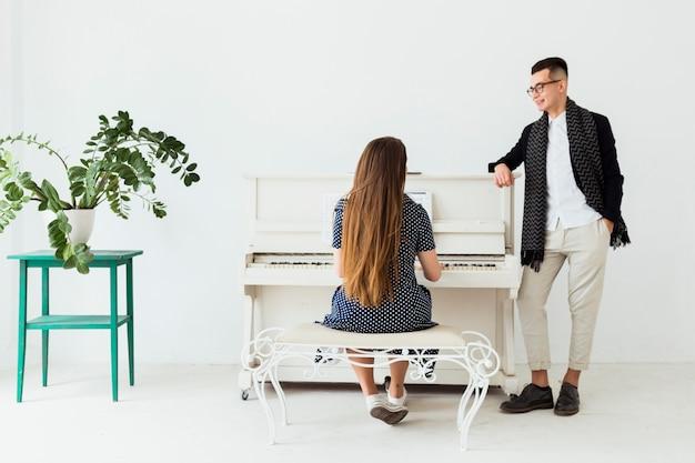 Heureux jeune homme avec la main dans sa poche, regardant la femme jouant du piano Photo gratuit