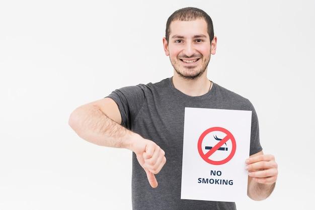 Heureux jeune homme ne tenant aucun signe de fumer montrant le pouce vers le bas isolé sur fond blanc Photo gratuit