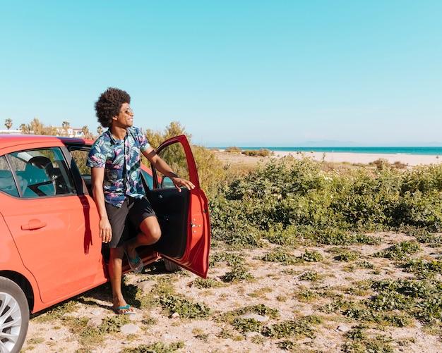 Heureux jeune homme noir sortir de la voiture sur la plage Photo gratuit