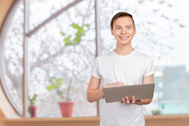 Heureux jeune homme avec ordinateur portable Photo Premium