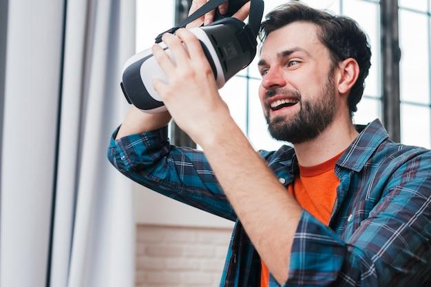 Heureux jeune homme portant des lunettes de réalité virtuelle Photo gratuit