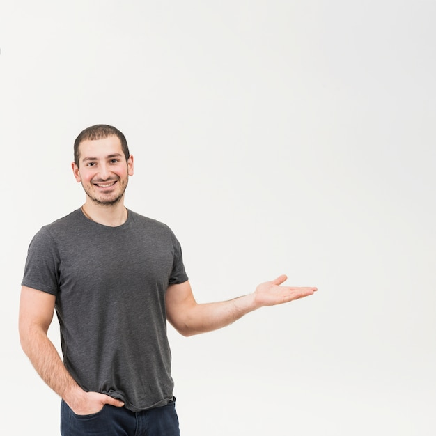 Heureux jeune homme présentant sur fond blanc Photo gratuit