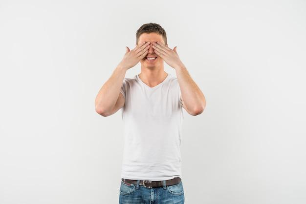 Heureux jeune homme qui couvre ses yeux avec deux mains sur fond blanc Photo gratuit