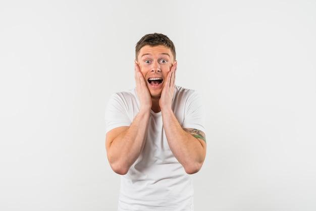 Heureux jeune homme avec ses deux mains sur les joues à la recherche d'un appareil photo sur fond blanc Photo gratuit