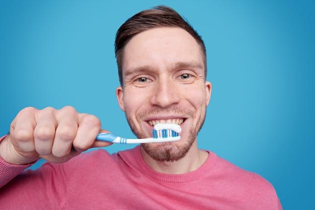 Heureux Jeune Homme Avec Un Sourire Sain Va Se Brosser Les Dents Tout En Tenant La Brosse à Dents Par La Bouche En Isolement Photo Premium
