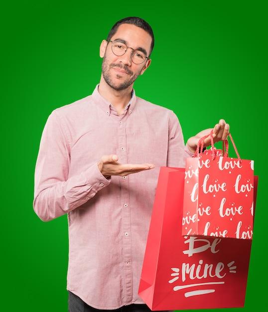 Heureux Jeune Homme Tenant Un Gros Coeur De Jouet Et Faisant Des Gestes à Propos De La Saint-valentin Photo Premium