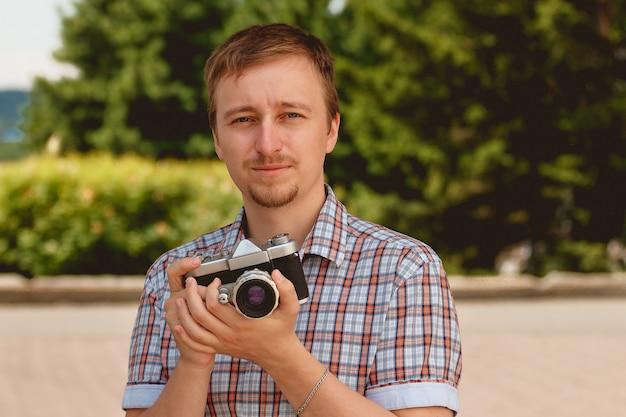 Heureux jeune homme tenant un photographe prenant des photos Photo Premium