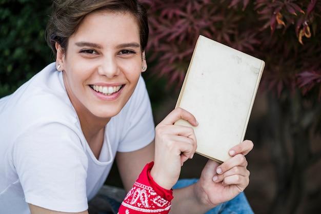 Heureux jeune livre montrant la femme Photo gratuit