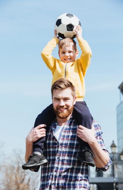 Heureux Jeune Père Portant Son Petit Fils Sur Les épaules Photo gratuit