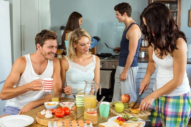 Heureux jeunes amis, cuisson des aliments dans la cuisine Photo Premium