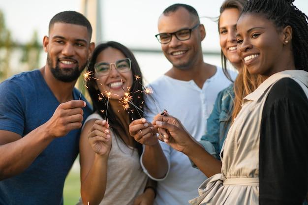 Heureux jeunes amis avec des feux de bengale Photo gratuit