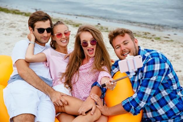 Heureux jeunes amis en lunettes de soleil, se reposer ensemble, prendre un selfie sur téléphone mobile Photo gratuit