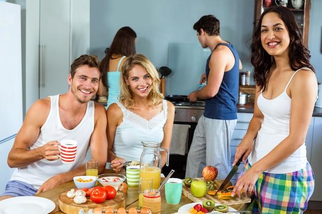 Heureux jeunes amis prépare le petit déjeuner dans la cuisine Photo Premium