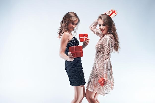 Heureux jeunes femmes qui dansent avec des cadeaux rouges dans les mains isolés sur blanc Photo Premium