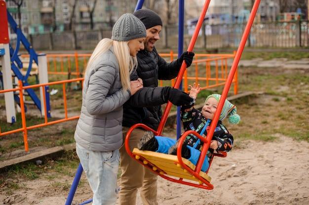 Heureux jeunes parents balançant un fils d'enfant en bas âge sur une balançoire Photo Premium