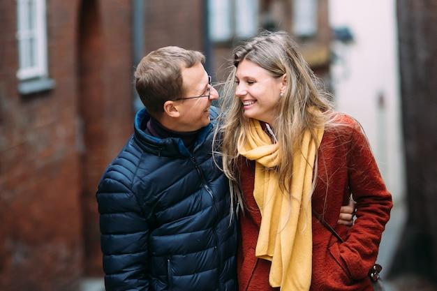 Heureux jeunes parents avec une poussette dans la rue de lubeck (allemagne) Photo Premium