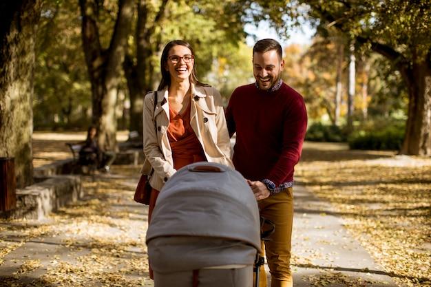 Heureux jeunes parents se promener dans le parc et conduire un bébé en landau Photo Premium