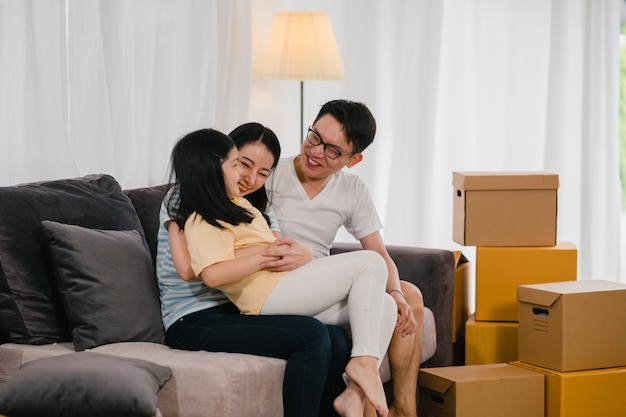 Heureux Jeunes Propriétaires Asiatiques Ont Acheté Une Nouvelle Maison. Une Mère Japonaise, Un Père Et Sa Fille S'embrassent Dans Le Nouveau Foyer Après Avoir Déménagé, Assis Sur Un Canapé Et Des Boîtes Ensemble. Photo gratuit