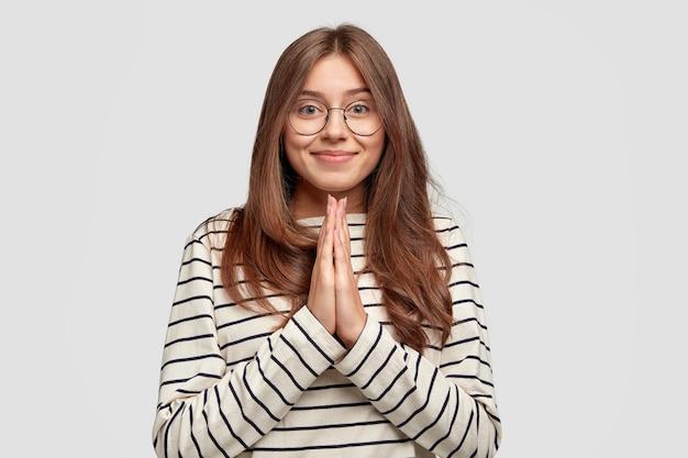 Heureux Jolie Femme Avec Un Sourire Doux, Garde Les Mains En Prière, Vêtu De Vêtements Rayés Photo gratuit