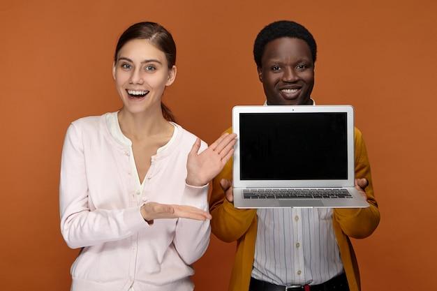 Heureux Joyeux Jeune Vendeur Afro-américain Et Sa Collègue à La Recherche Amicale Excitée Debout à Côté De L'autre, Annonçant Tout Nouveau Gadget électronique Portable Générique Et Souriant Photo gratuit