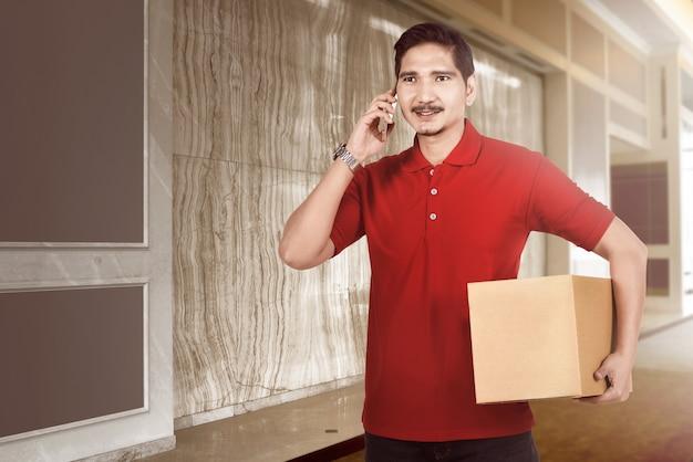 Heureux livreur asiatique avec colis à l'aide de téléphone portable Photo Premium