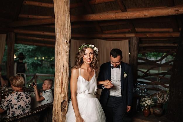 Heureux mariés et leur première danse, mariage dans l'élégant restaurant avec une lumière et une atmosphère merveilleuses Photo Premium