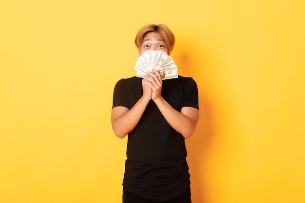 Heureux Mec Asiatique Blond Chanceux Se Réjouissant De Gagner De L'argent, Détenant De L'argent Et à La Recherche De Mur Jaune Heureux, Debout Photo gratuit
