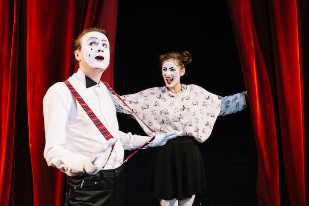 Heureux mime féminin en regardant le mime masculin tenant le jarretelle sur scène Photo gratuit