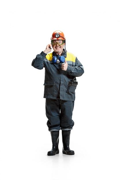Heureux Mineur Mâle Barbu Debout à La Caméra Avec Smartphone Sur Fond Blanc Photo gratuit