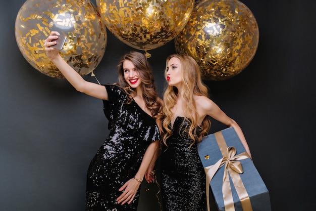 Heureux Moments De Fête De Deux Jeunes Femmes à La Mode Faisant Selfie. Robe Noire De Luxe, Longs Cheveux Bouclés, Gros Ballons Avec Des Guirlandes Dorées, Présent, S'amusant, Souriant. Photo gratuit