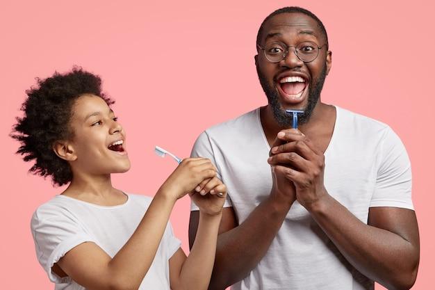 Heureux Papa Et Fils Joyeux à La Peau Sombre Tiennent Le Dentifrice Et Le Rasoir, Ont La Routine Matinale Ensemble Photo gratuit