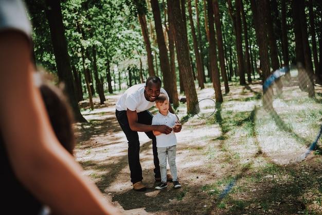 Heureux parents apprennent à leurs enfants à jouer au badminton dans un parc Photo Premium