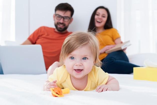 Heureux parents et bébé au lit Photo gratuit
