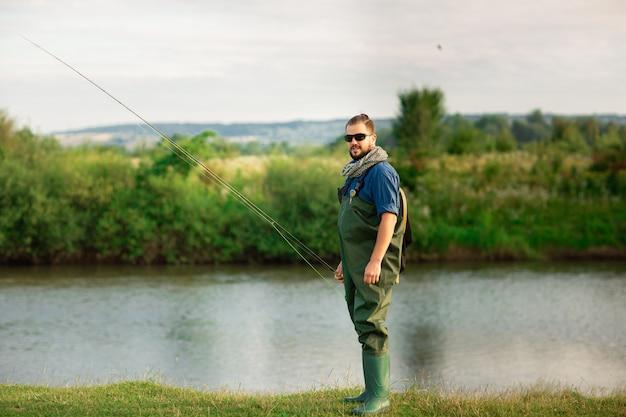 Heureux pêcheur avec costume spécial et canne à pêche près de la rivière Photo Premium