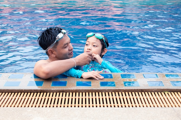 Heureux père asiatique prend soin de sa fille dans la piscine Photo Premium