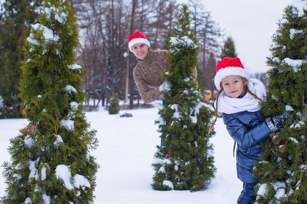 Heureux père et enfant en chapeaux santa avec arbre de noël en plein air Photo Premium