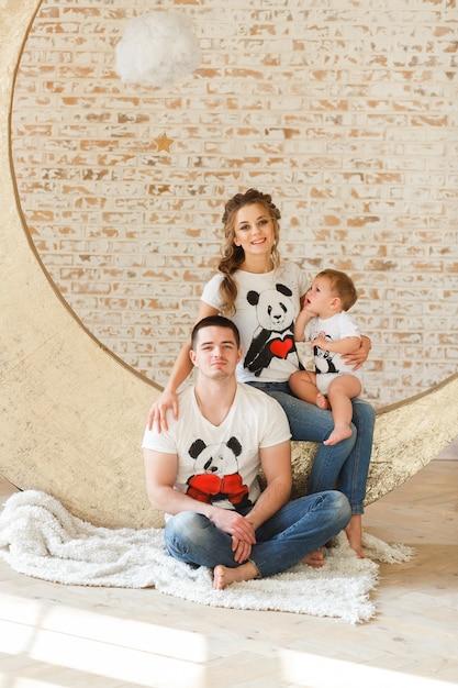 Heureux père de famille, mère et fils près d'un mur de briques blanches dans la chambre. Photo gratuit