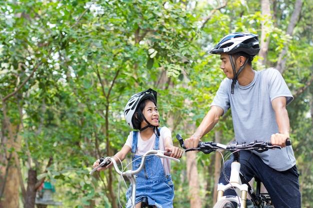 Heureux père et fille faisant du vélo dans le parc Photo Premium