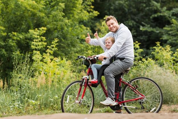 Heureux père et fille en vélo Photo gratuit