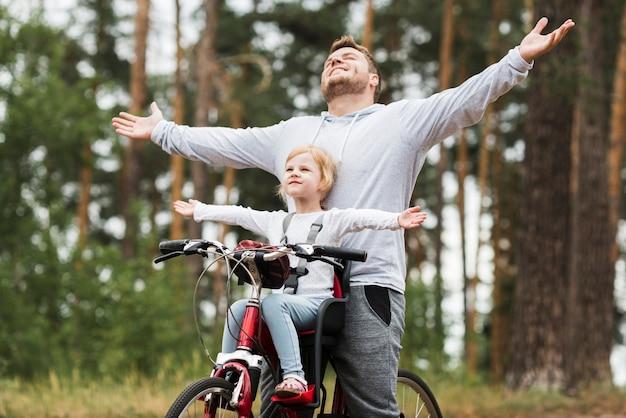 Heureux père et fille à vélo Photo gratuit