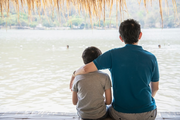Heureux père et fils pendant des vacances à la nature du site de l'eau Photo gratuit