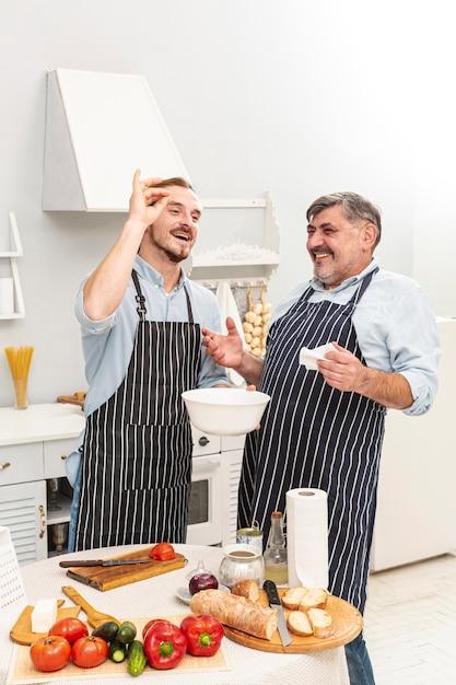 Heureux père et fils préparant un délicieux repas Photo gratuit