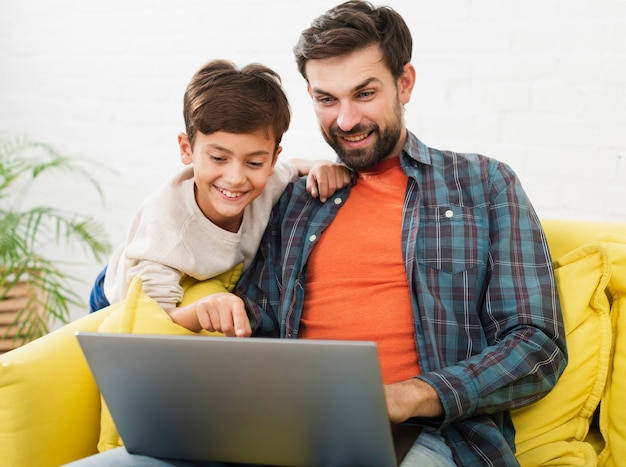 Heureux père et fils à la recherche sur un ordinateur portable Photo gratuit