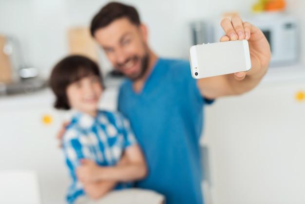 Heureux père et fils utilisant un smartphone à la maison. Photo Premium