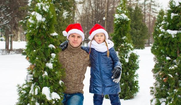 Heureux père et petite fille à santa chapeaux avec arbre de noël en plein air Photo Premium